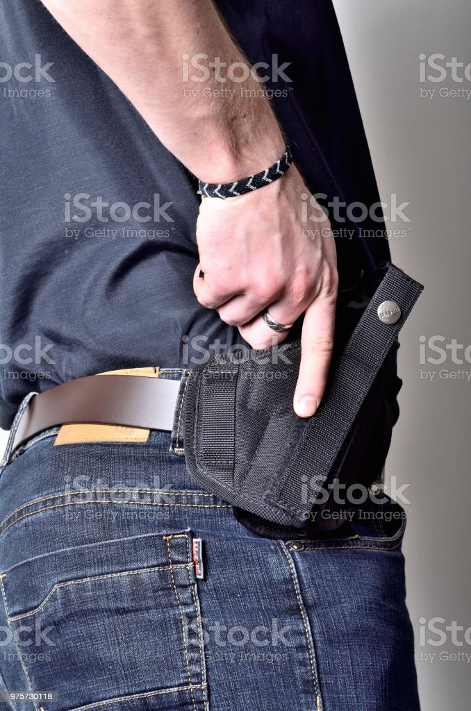 Man pulling out a pistol gun from the holster on belt, blue jeans, black shirt stock photo