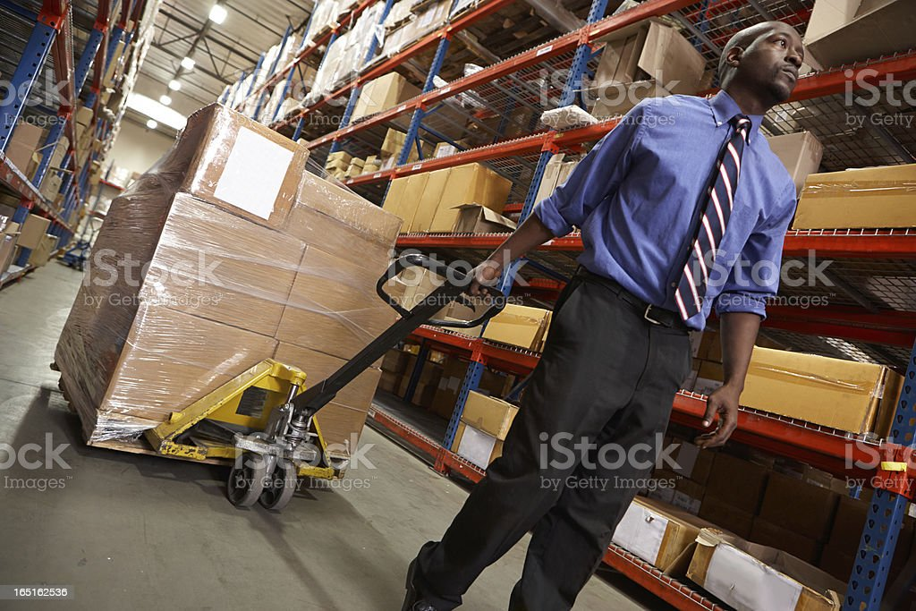 Man Pulling Pallet In Warehouse royalty-free stock photo