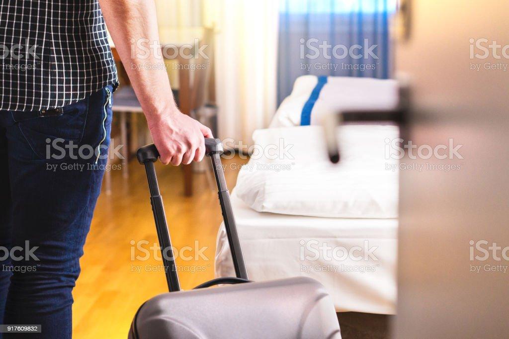 Hombre tirando de maleta y entrar en la habitación del hotel. Viajero va a la habitación o caminando dentro de motel con equipaje. - foto de stock