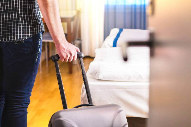 man pulling suitcase and entering hotel room. traveler going in to room or walking inside motel with luggage. - casa in affitto foto e immagini stock