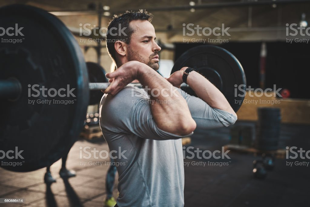 Man pulling up large barbell in fitness class stock photo