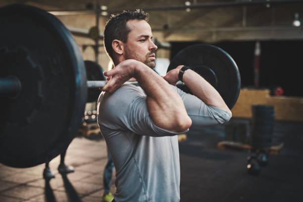 man zieht sich große langhantel in fitness-klasse - hals übungen stock-fotos und bilder