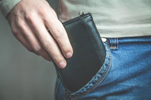 schwarze geldbörse zieht aus seiner tasche jeans mann. - leder portemonnaie herren stock-fotos und bilder