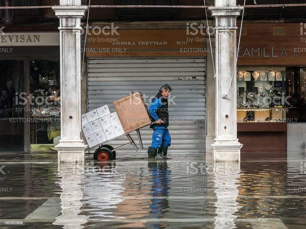 Man pulls his trolley through flood waters in Venice stock photo