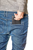 A man in jeans pulls out a black leather purse from his back pocket