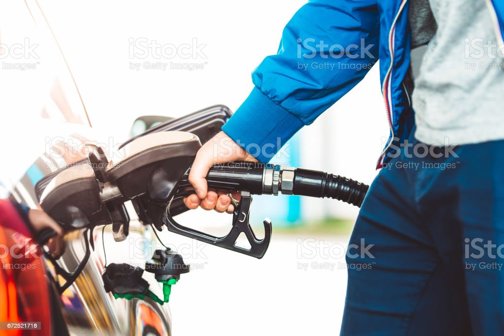 Man pumping fuel in car at gas station stock photo