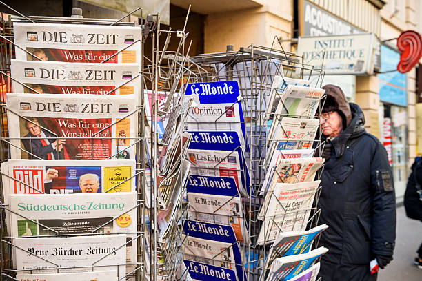 man purchases a international press newspapers from a newsstand - donald trump us president стоковые фото и изображения