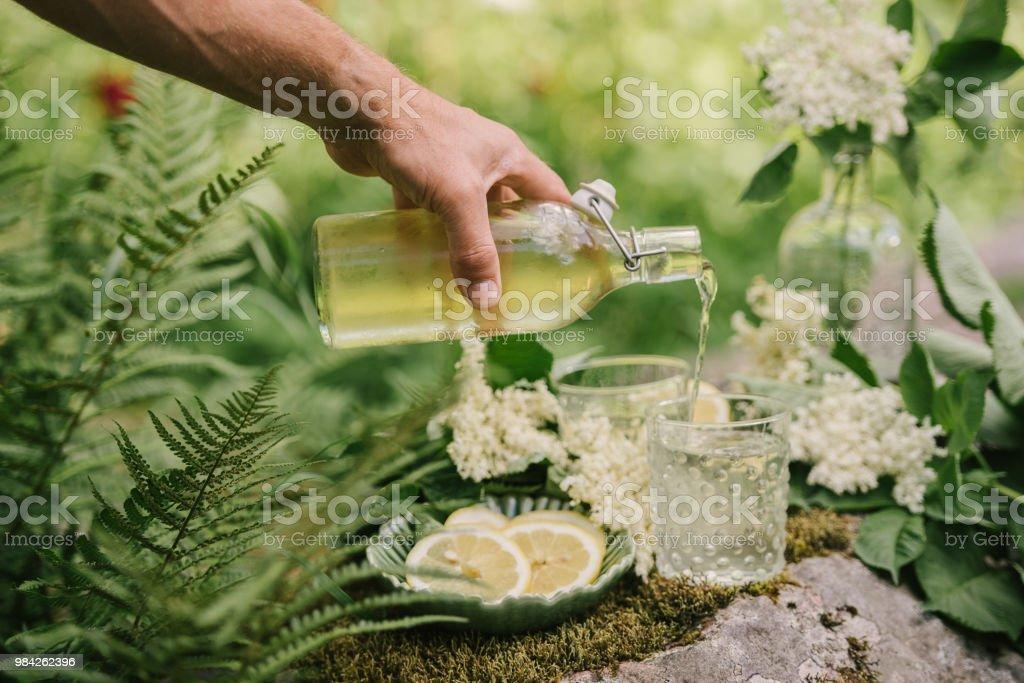 Man puring elderflower cordial juice lemonade outdoors in summer sunlight stock photo