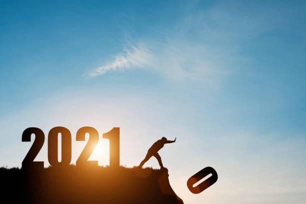 el hombre empuja el número cero por el acantilado donde tiene el número 2021 con el cielo azul y el amanecer. es símbolo de inicio y bienvenida feliz año nuevo 2021. - año nuevo fotografías e imágenes de stock