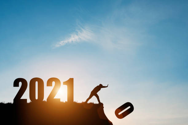 man push number zero down the cliff where has the number 2021 with blue sky and sunrise. it is symbol of starting and welcome happy new year 2021. - new year imagens e fotografias de stock
