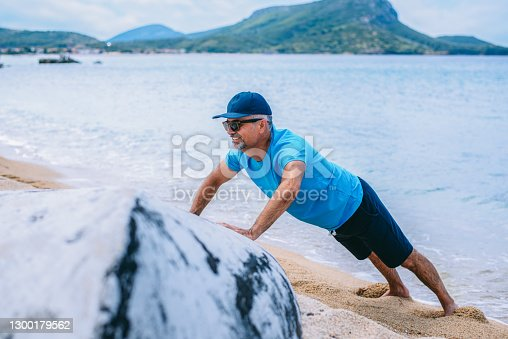 Mature man push up workout outside by the sea