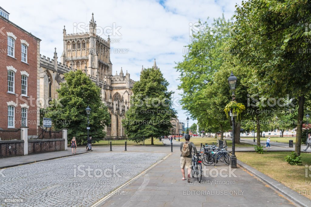 Man pushes a bicycle along a road near Bristol Cathedral stock photo