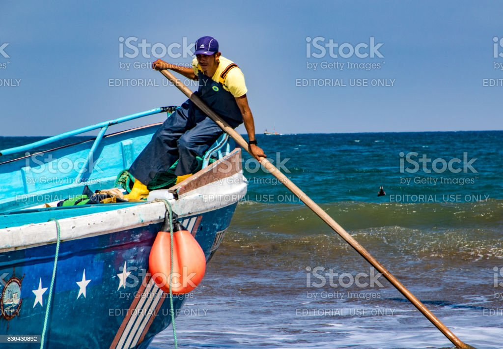 Man pushes against sand to release boat from the surf in Puerto Lopez, Ecuador stock photo