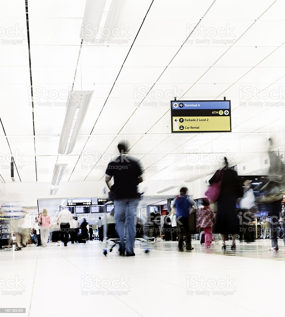 Man pushes luggage cart through airport concourse royalty-free stock photo