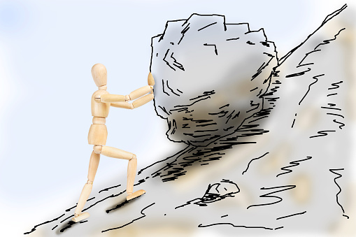 Man pushing a stone up to the mountain slope. Abstract image with a wooden puppet