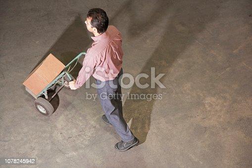 Man pushing cart in warehouse