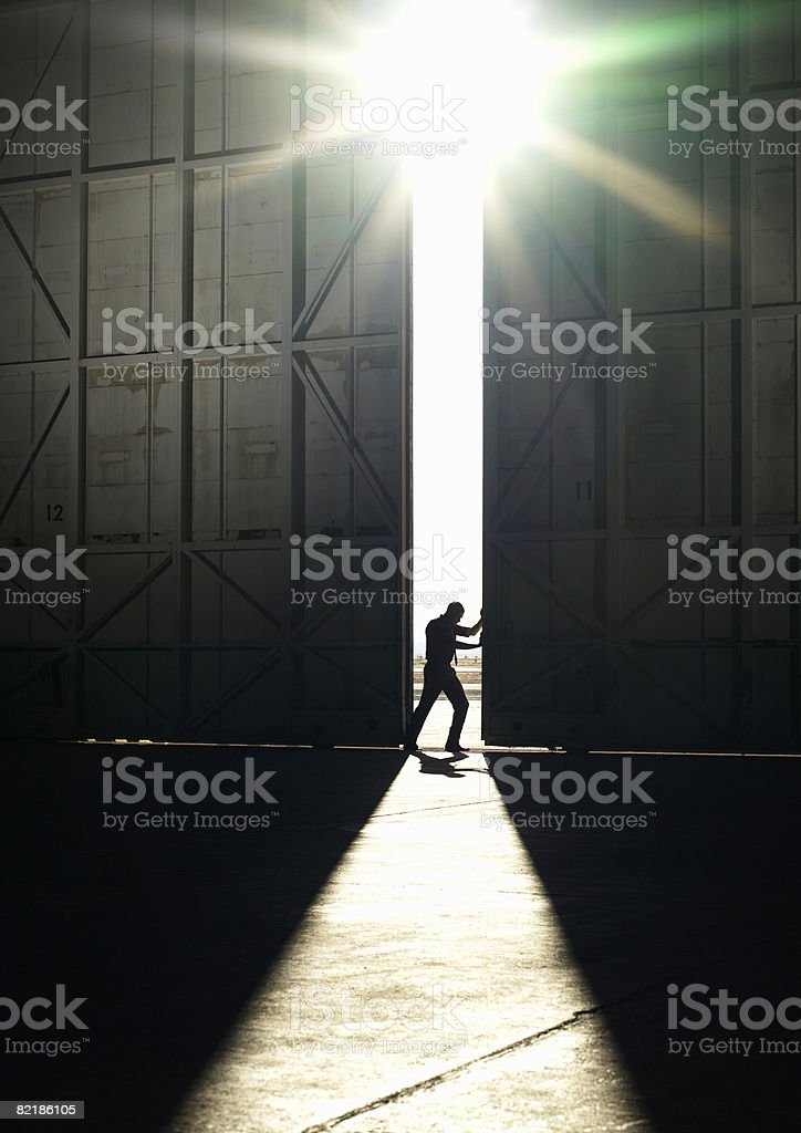 man pushing door open stock photo