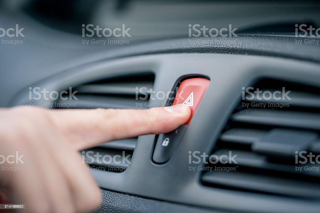 Man Pushing Hazard Lights Button on Car Dashboard stock photo