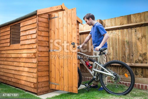 A young man pushing his bicycle into a shed for storage.