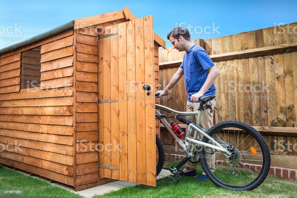 Man pushing his bike into a shed. stock photo