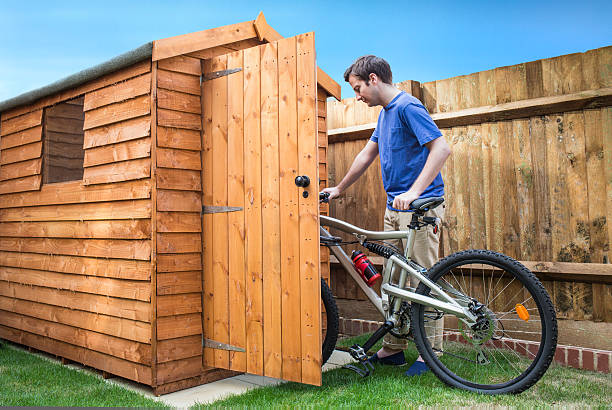 Man pushing his bike into a shed. A young man pushing his bicycle into a shed for storage. shed stock pictures, royalty-free photos & images