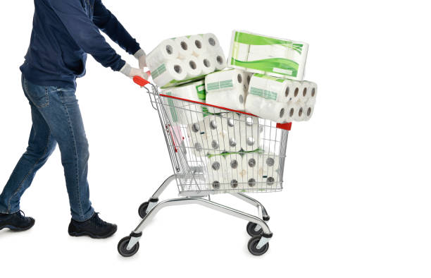 Man Pushing Shopping Cart Full of Toilet Paper Packages stock photo