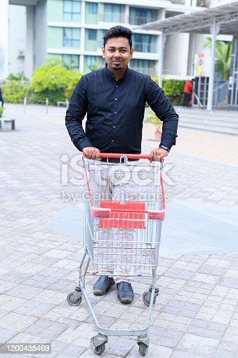 Man pushing shopping trolley outside the supermarket in India, shopping concept