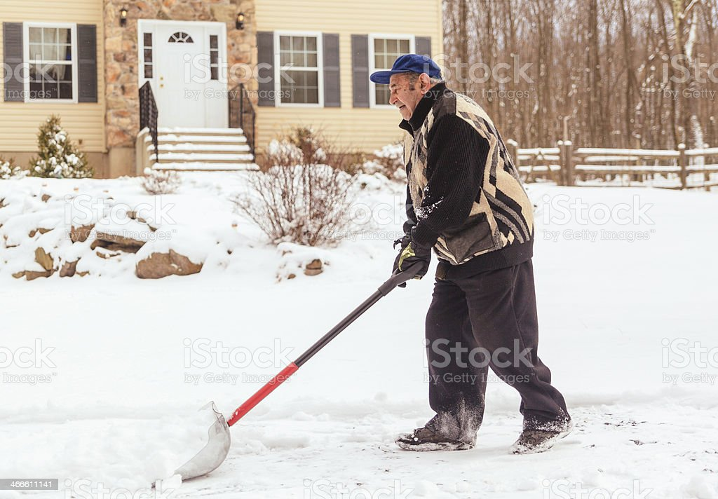 Man pushing snow with shovel in front of house stock photo