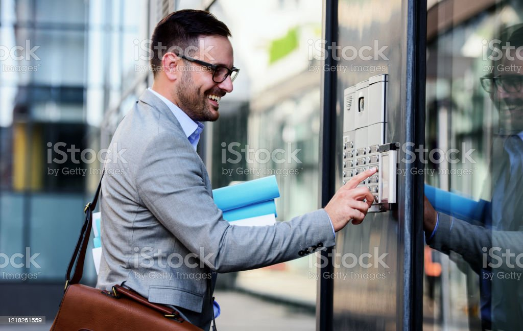Man pushing the button and talking on the intercom Businessman pushing the button and talking on the intercom in front of the firm Adult Stock Photo