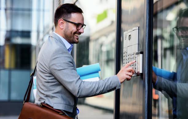 Mann drückt den Knopf und spricht auf der Gegensprechanlage – Foto