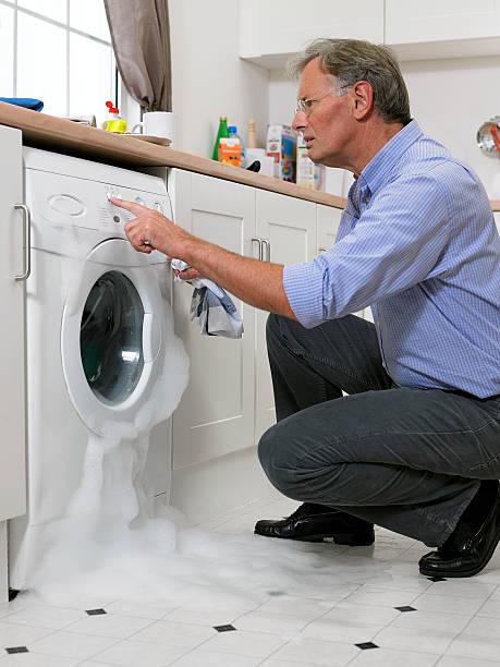 Man pushing washing machine as it overflows stock photo