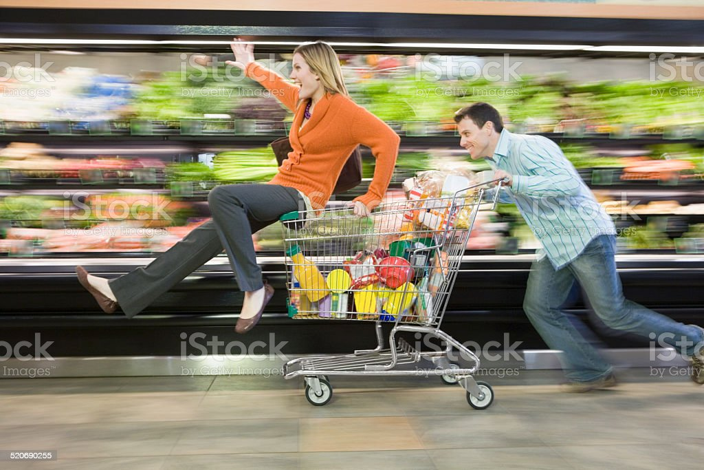 Man pushing woman in supermarket trolley, blurred motion stock photo