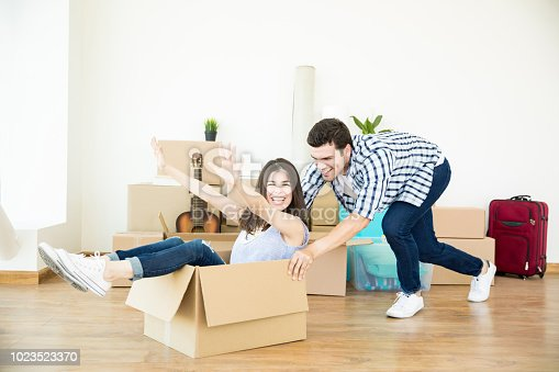 istock Man Pushing Woman Sitting In Cardboard Box In New Home 1023523370