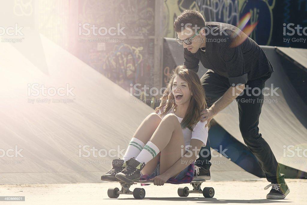 Man pushing woman sitting on skateboard stock photo