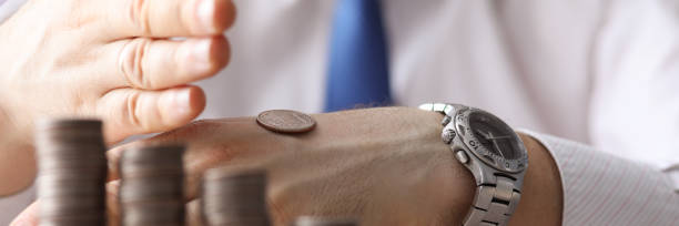 Man put coin on back his hand, counting money stock photo