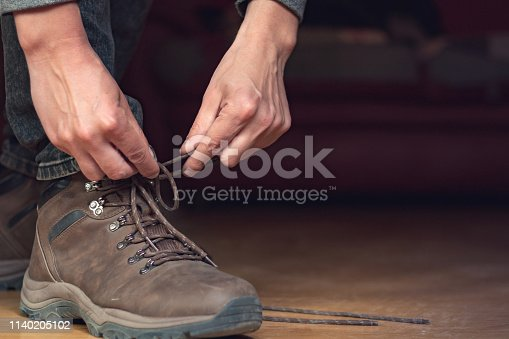 Man puts his brow leather boots on, he ties long shoe lace