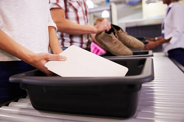 Man Puts Digital Tablet Into Tray For Airport Security Check stock photo