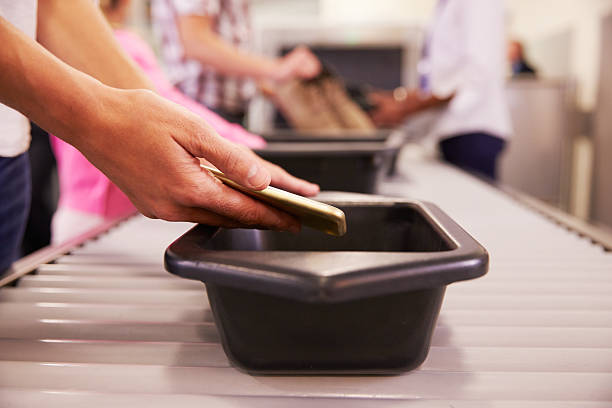 Man Puts Mobile Phone Into Tray For Airport Security Check stock photo