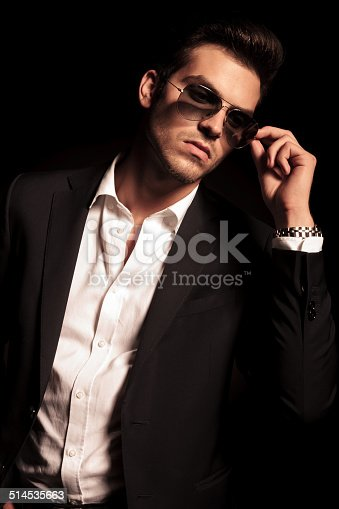 907934274 istock photo man puts on his sunglasses and looks to side 514535663