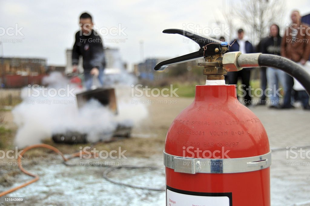 Man puts out fire outside by using a extinguisher stock photo