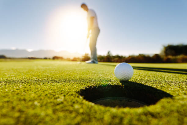 man puts the ball on golf course green - golf stock photos and pictures
