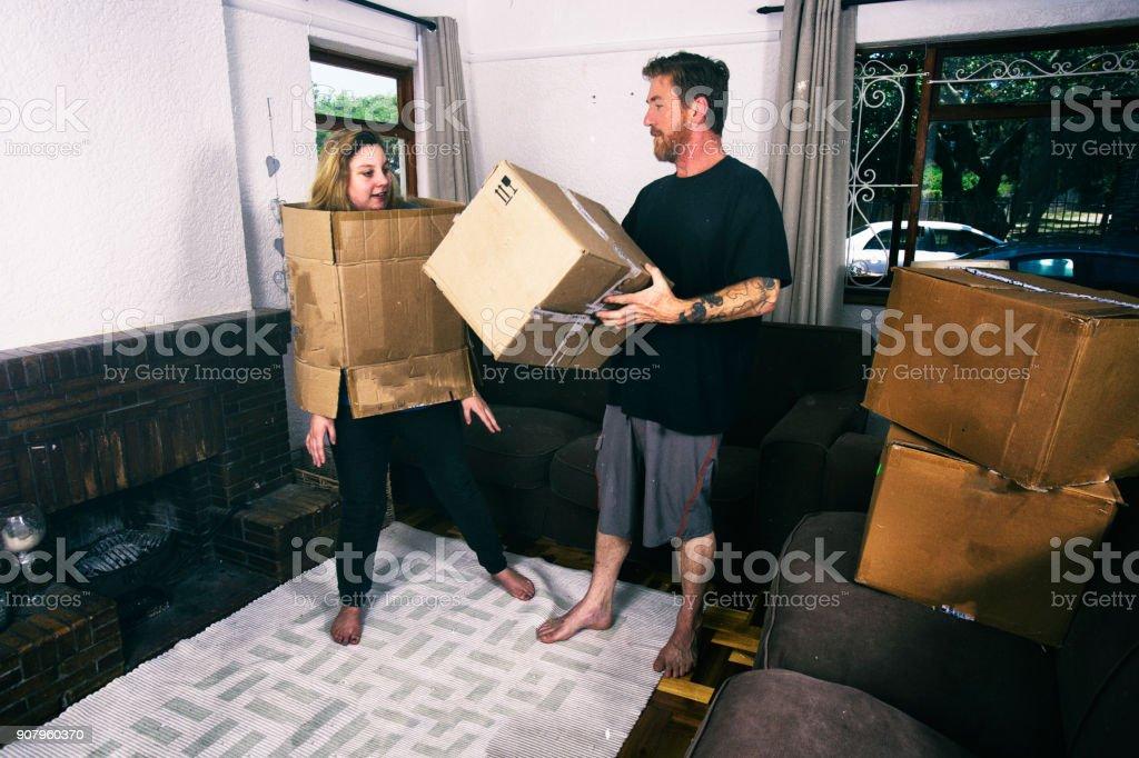 男が女性を段ボール箱の内部に置く ストックフォト