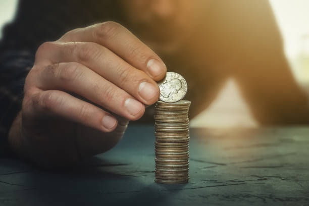Man putting a coin with the word liberty on a money stack. Finance, banking, savings, personal budget, liberalism, increase in wealth concepts. stock photo