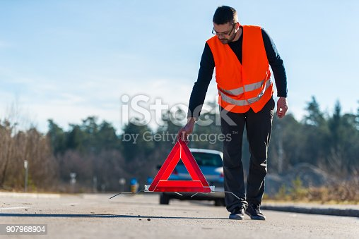 istock A man putting a warning triangle behind his car 907968904