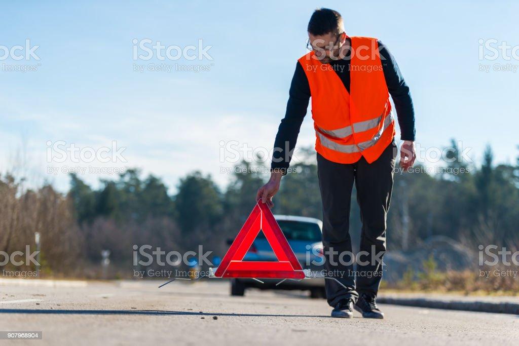 Un homme mettre un triangle de présignalisation derrière sa voiture - Photo
