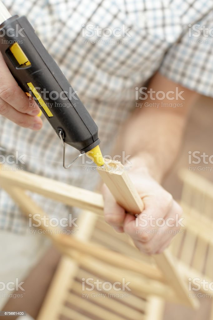 Man putting an electric hot glue gun for wooden furniture stock photo