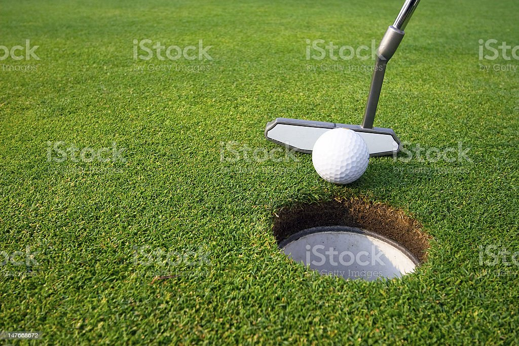 Man Putting Ball into Hole on Golf Course - Vertical stock photo