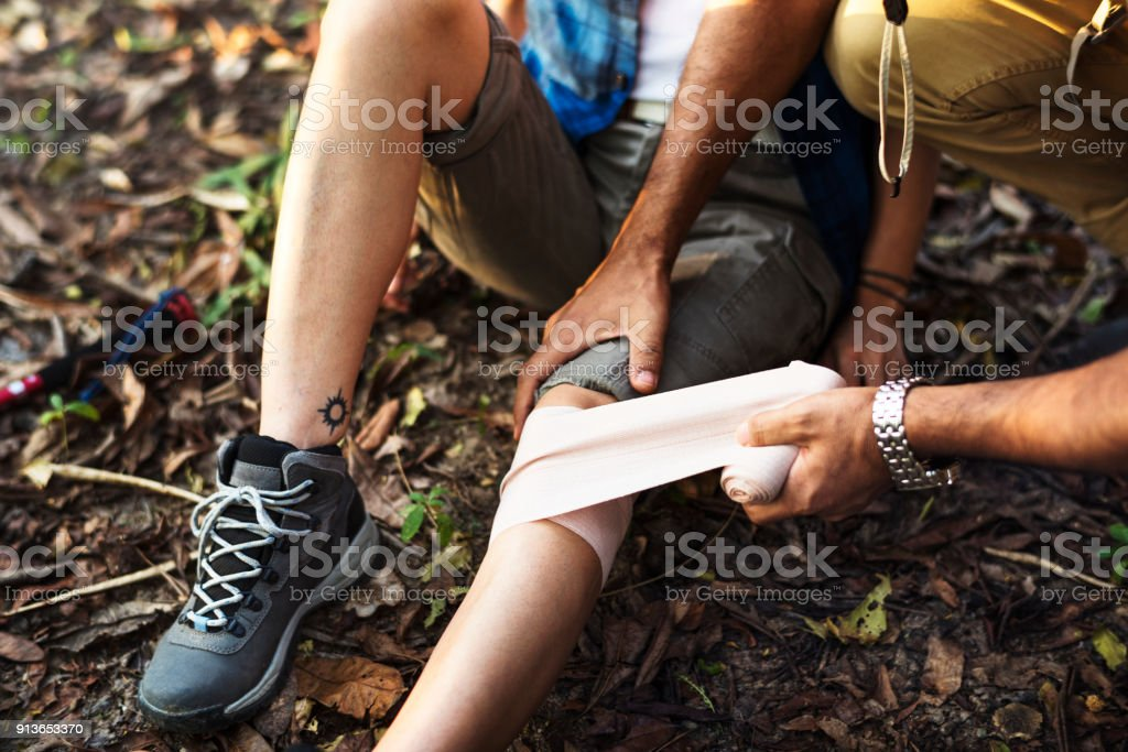 Man putting bandage on his partner's knee in the jungle stock photo