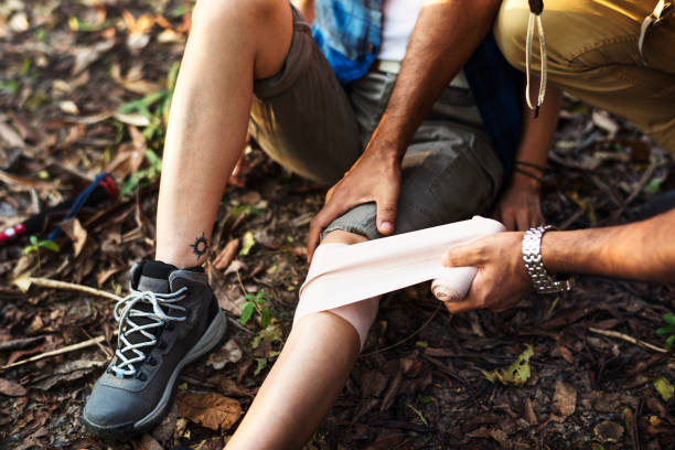 man putting bandage on his partner's knee in the jungle - first aid stock photos and pictures
