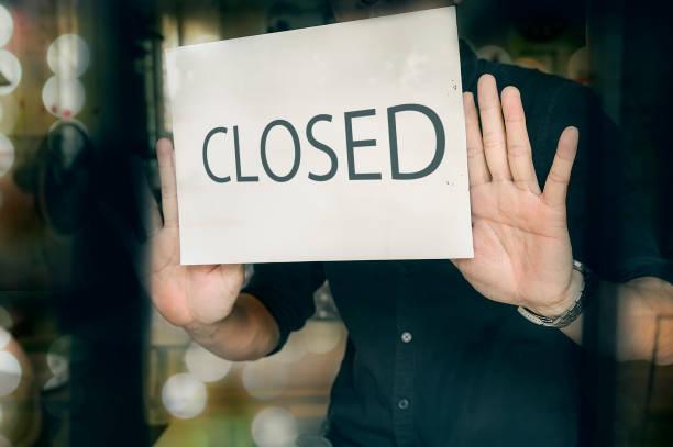homem que põr o sinal fechado no indicador na loja. tarde da noite na cidade. - fechado - fotografias e filmes do acervo